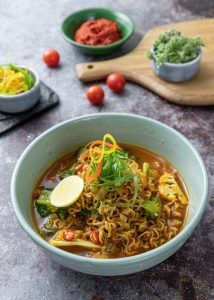 Chili noodle soup with fresh vegetables on top