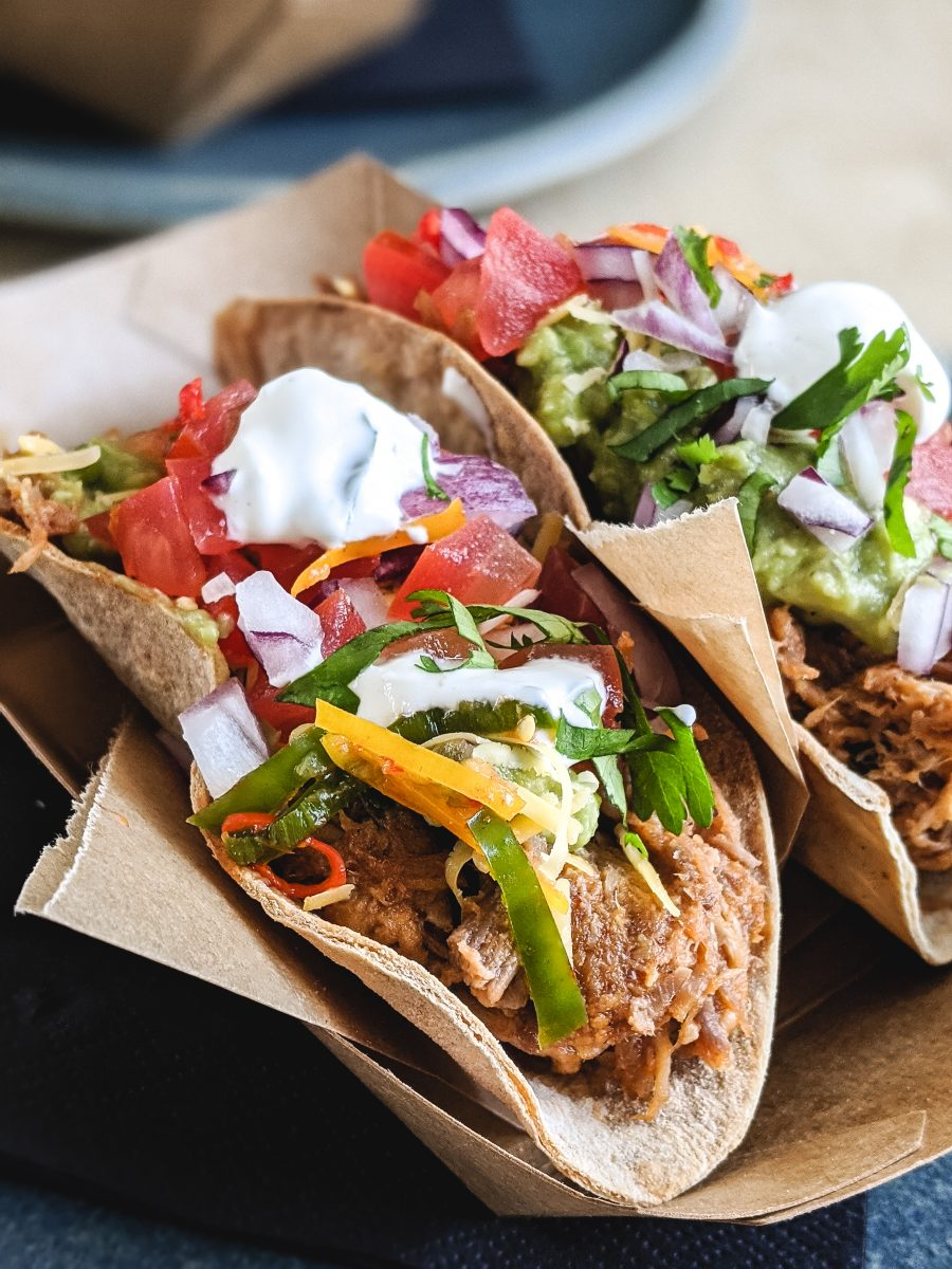 Tacos with pulled pork, fresh vegetables and cream