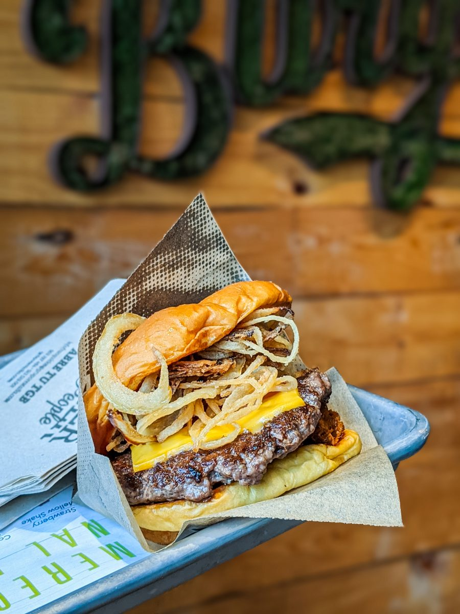 Cheese burger with fried onion on a tray