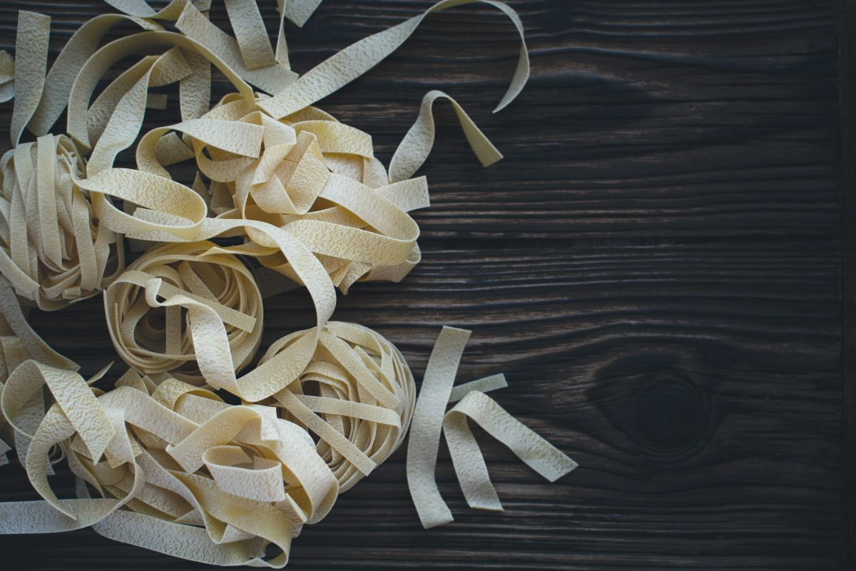 Pasta tagliatelle on a wooden background