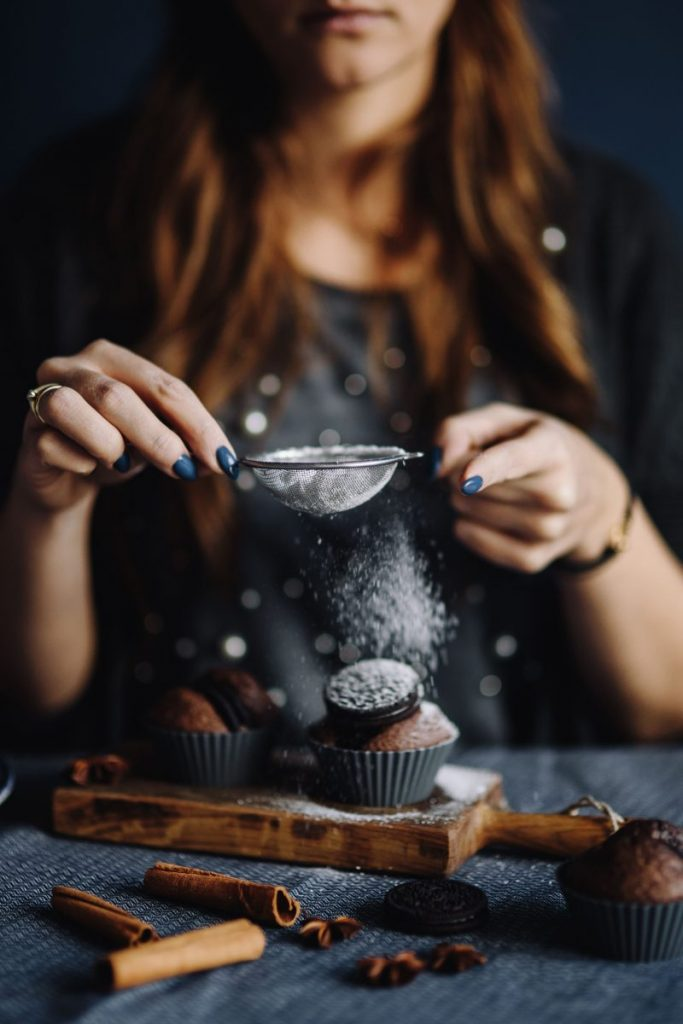 Woman dusting muffins with a powdered sugar