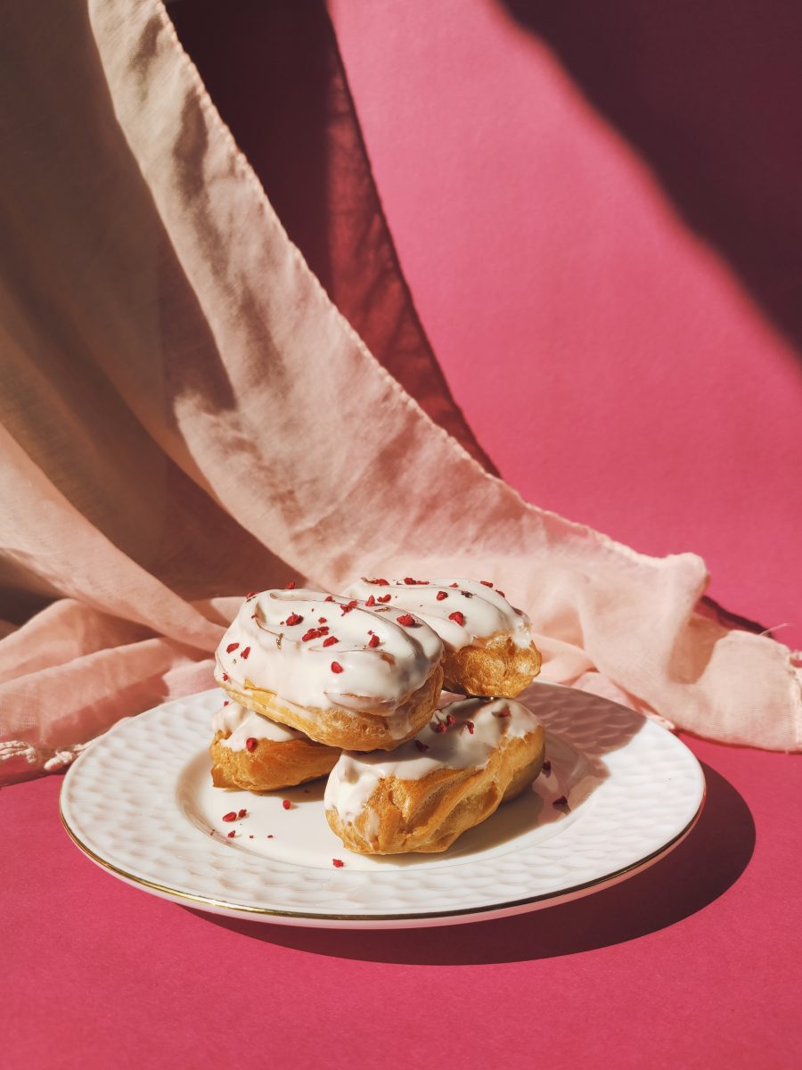 Delicious eclairs on a plate decorated with dried raspberries