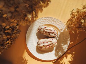 Delightful eclairs with white glaze and raspberry crumb